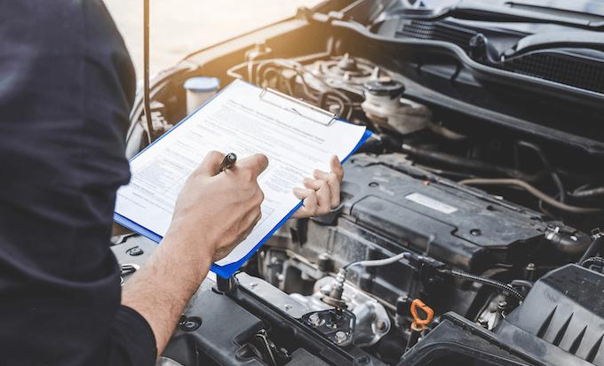 車の修理のため確認する男性